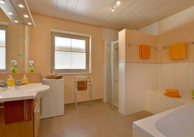 Badezimmer mit Dusche und Badewanne sowie Waschmaschine
