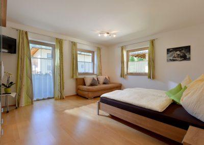 Schlafzimmer mit ausziehbarer Schlafcouch und TV